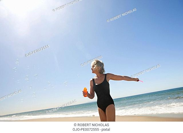 Senior woman blowing bubbles on beach