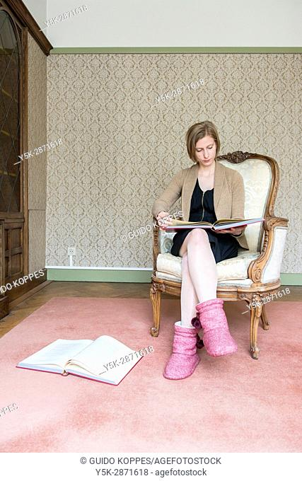 Tilburg, Netherlands. Portrait woman reading part of the Holy Bible while sitting in her reading room library chair