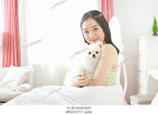 Portrait of young smiling woman hugging her puppy in blanket