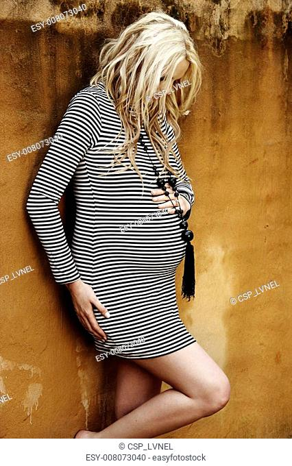 Beautiful eight months pregnant blond woman with curly hair in a black and white stripes fashion mini dress against a grunge wall background