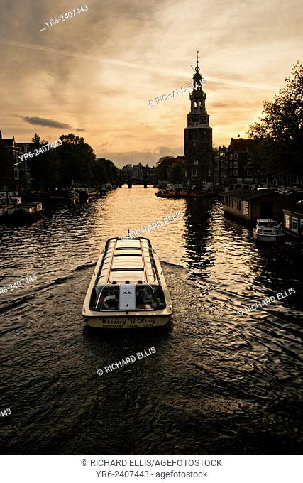 A sightseeing boat travels down the Oudeschans canal with Montelbaanstoren Tower near Prins-Hedrichkade at sunset in Amsterdam