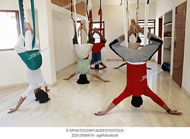 An aerial yoga class practicing Supta Baddha Konasana