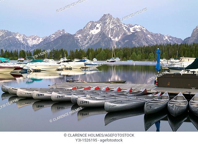 The sky begins to lighten over Mount Moran and the still surface of Jackson Lake and Colter Bay, full of sleeping boats and canoes in Grand Teton National Park