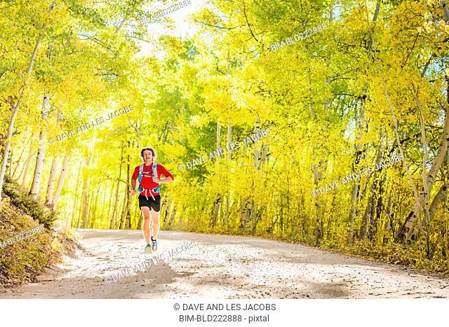 Caucasian man running on forest path
