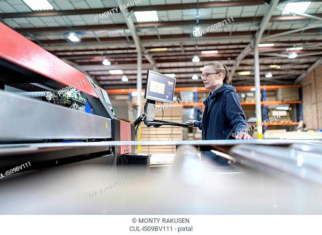 Female printing machine operator in cardboard box factory
