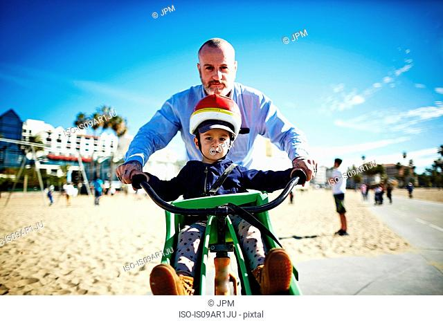 Father guiding son on bicycle at beach, Brooklyn, New York, USA
