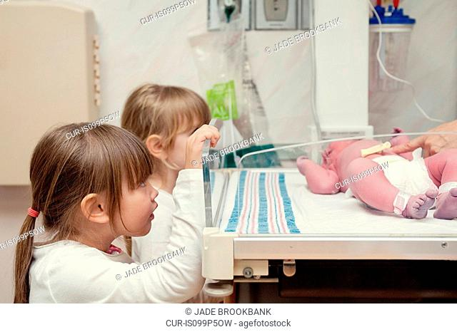 Two sisters looking at newborn baby sister