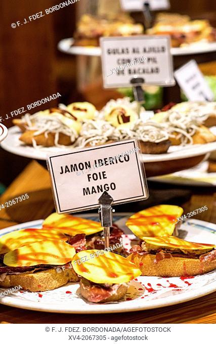 Jamón ibérico con foie y mango (Iberian ham with foie and mango). Typical Pintxos, also called tapas at popular San Sebastian bar, Basque Country, Spain