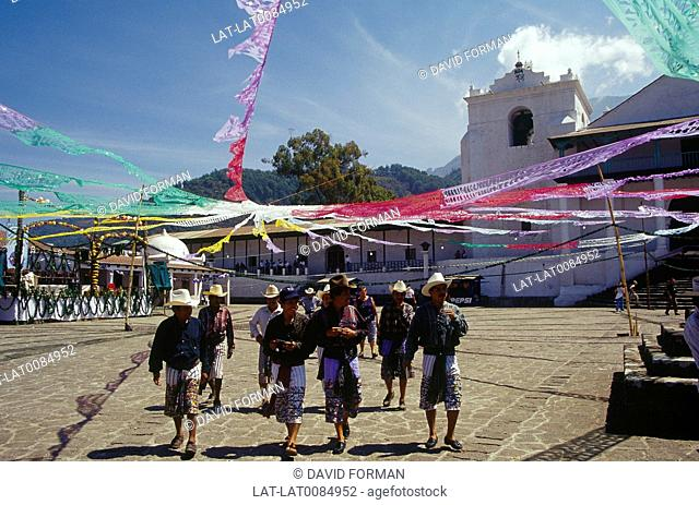Santiago village. Men in square under coloureds streamers. Traditional male dress. Hats,long shorts