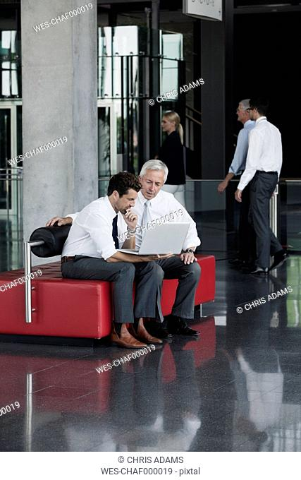Two businessmen with laptop in office lobby