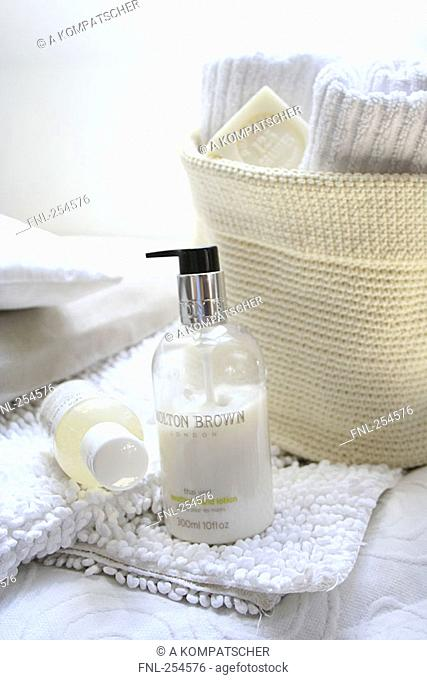 Close-up of bottles of moisturizers on towel
