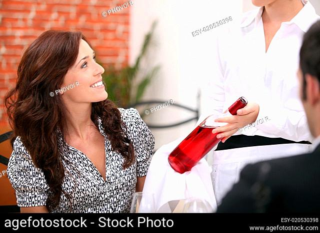 Waitress presenting bottle of wine to couple