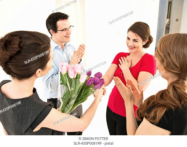 Business people giving colleague flowers