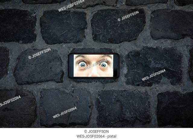 Cell phone image with eyes wide open on cobblestone pavement