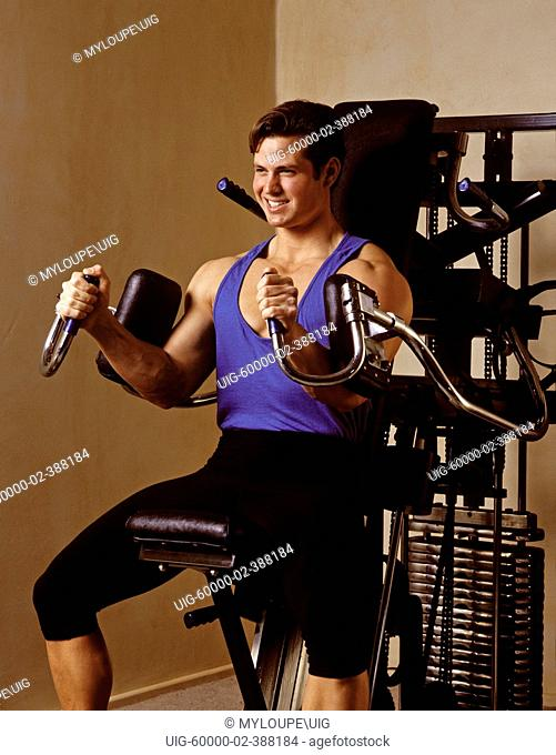 A young man BA young man BODY BUILDS using WEIGHT TRAINING EQUIPMENT - MODEL RELEASED
