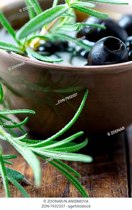 Black olives in clay bowl and rosemary set