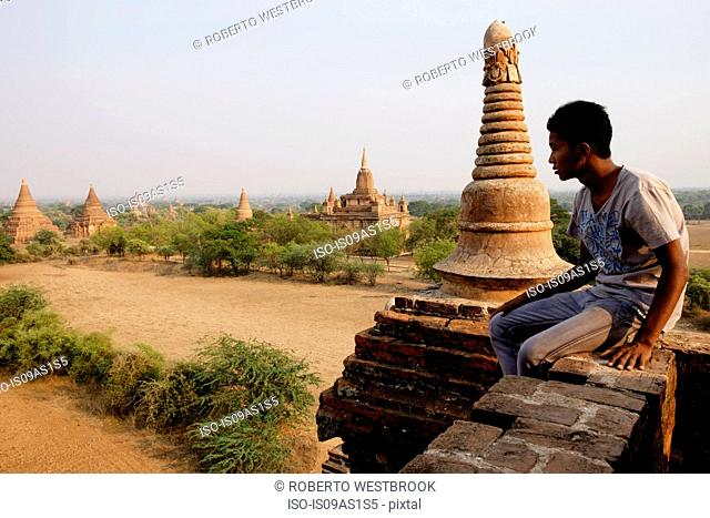 Man sitting on stone wall, Bagan Archaeological Zone, Buddhist temples, Mandalay, Myanmar