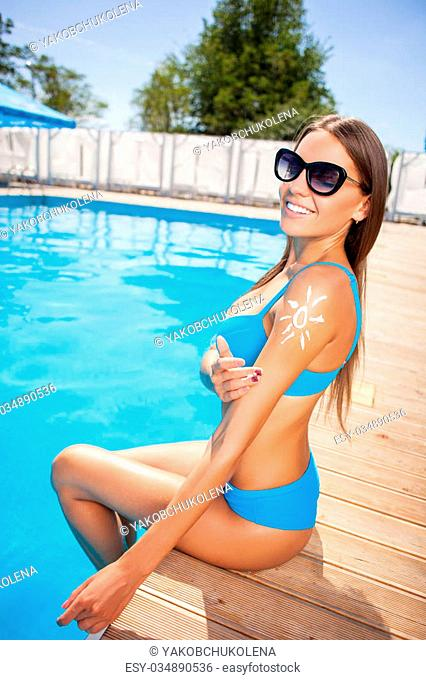 Attractive girl is sitting and putting her legs in swimming pool. She is sunbathing and smiling. The lady applying cream on her arm in form of the sun