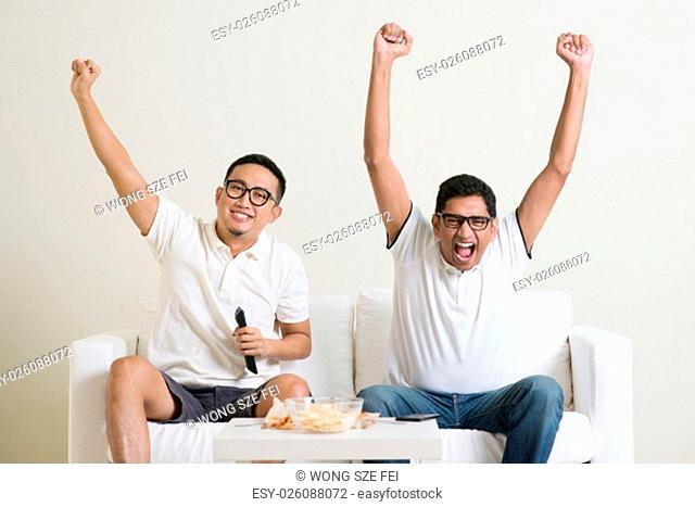 Cheerful group of friends watching football game on tv at home
