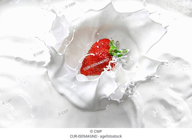 Strawberry splashing into cream