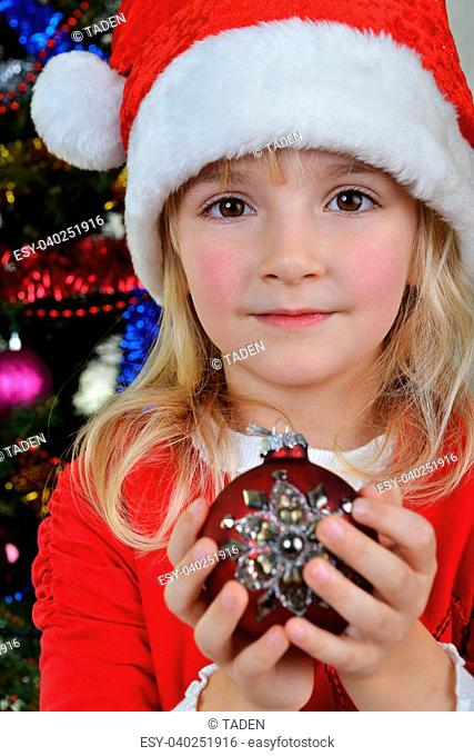 adorable little girl holding christmas ball near Christmas fir-tree
