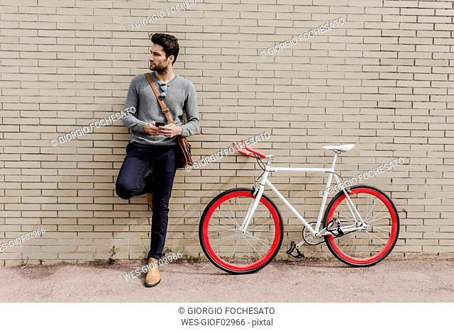 Portrait of young man with racing cycle and cell phone leaning against wall
