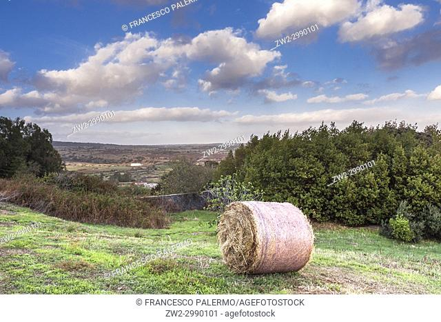 Scenic view of bale of hay dominates the valley against a dramatic sky. Bonarcado, Sardinia. Italy