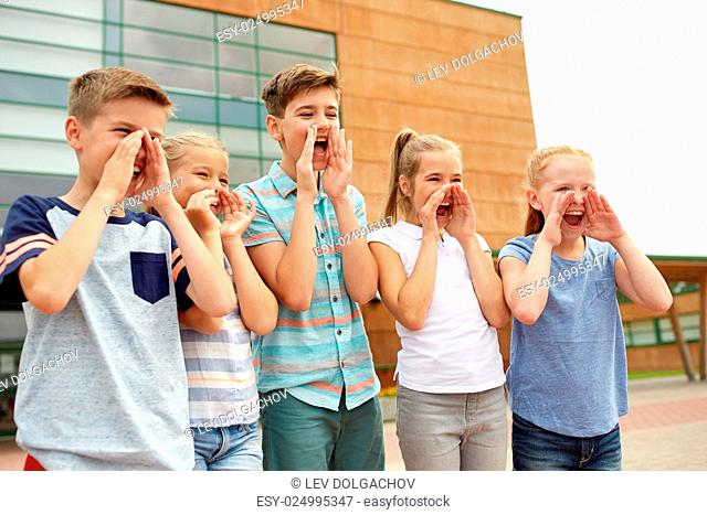 primary education, friendship, childhood and people concept - group of happy children or elementary school students calling or shouting outdoors