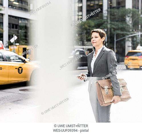 USA, New York City, businesswoman in Manhattan with cell phone