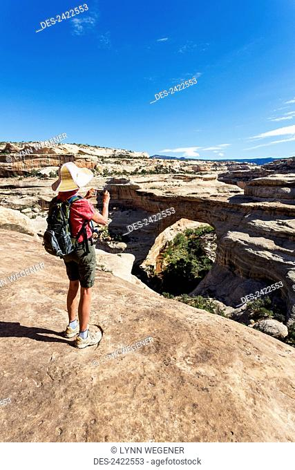 A female hiker takes a photo with a smart phone of the rock bridge named Sipapu in the Natural Bridges National Monument; Utah, United States of America
