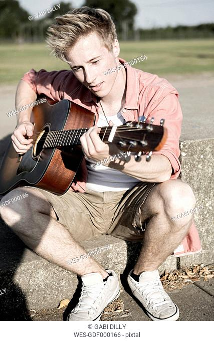 Germany, Young man playing guitar in park