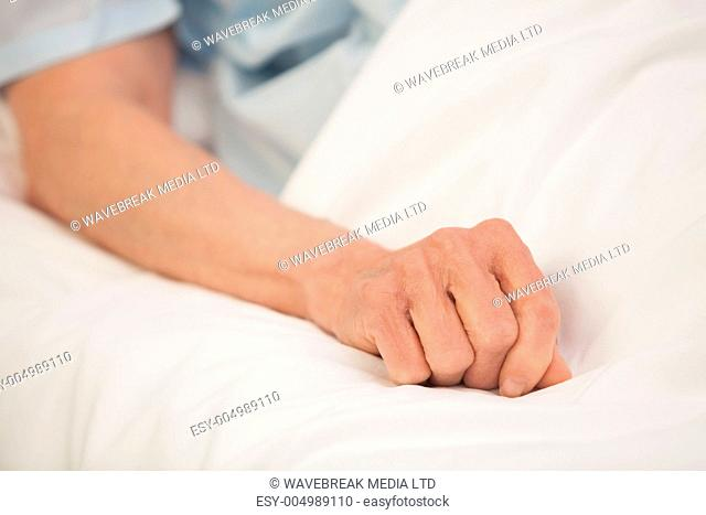 Elderly arm outstretched in hospital bed
