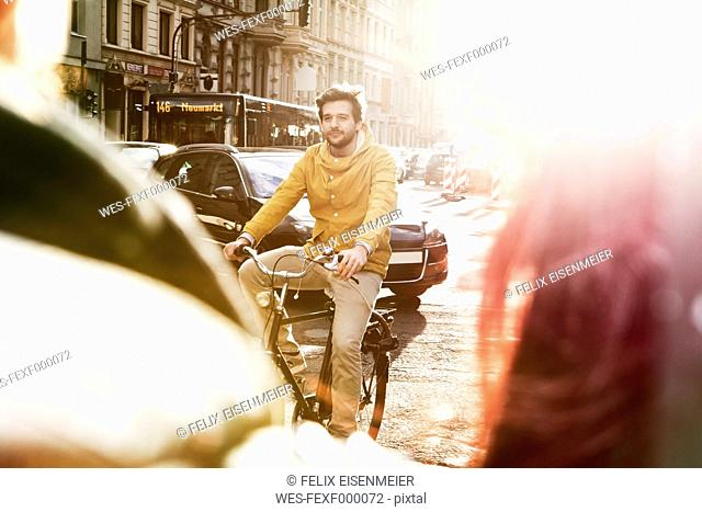 Germany, North Rhine-Westphalia, Cologne, young man riding bicycle