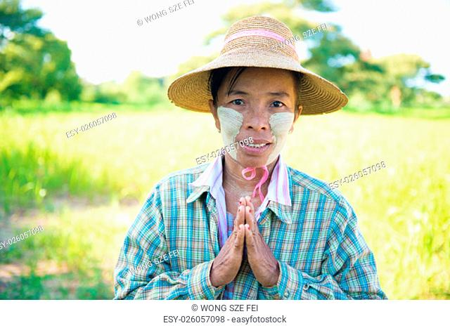 Portrait of a mature Burmese female farmer with thanaka powdered face in blessing gesture