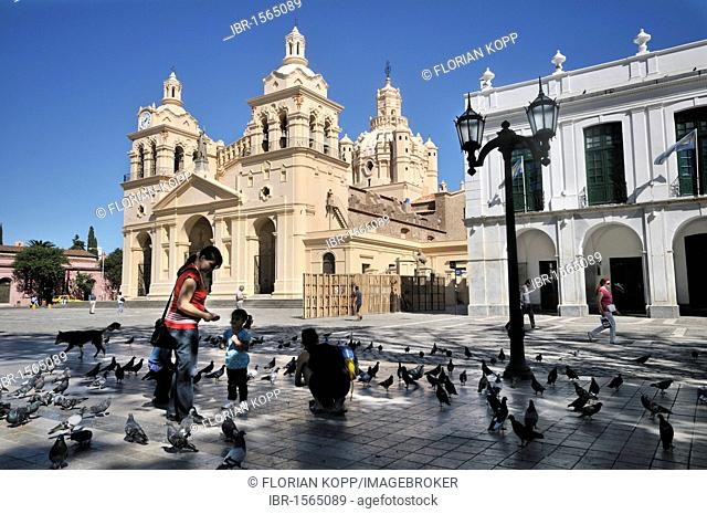 Mothers and children feeding pigeons in the San Martin Praza square in front of the cathedral Iglesia Catedral, Cordoba, Argentina, South America