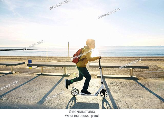 Boy riding scooter on beach promenade at sunset