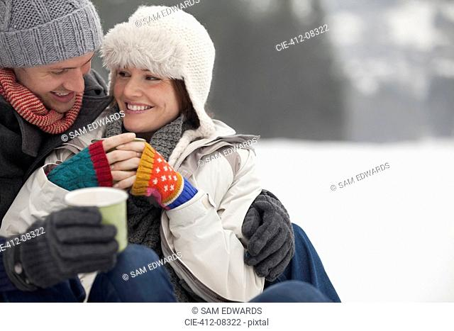 Happy couple drinking coffee in snow