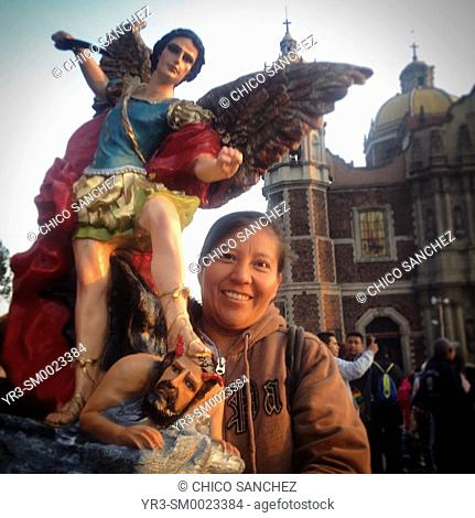 A woman holds an image of Saint Michael Archangel during the annual pilgrimage to the Our Lady of Guadalupe basilica in Mexico City, Mexico