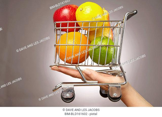 Caucasian woman holding miniature shopping cart with fruit