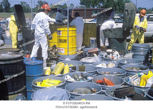 Workers handling toxic household wastes at waste cleanup site on Earth Day