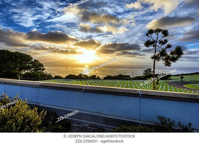 The Sun setting through clouds over the Pacific Ocean. View from Fort Rosecrans National Cemetery, San Diego, California, United States
