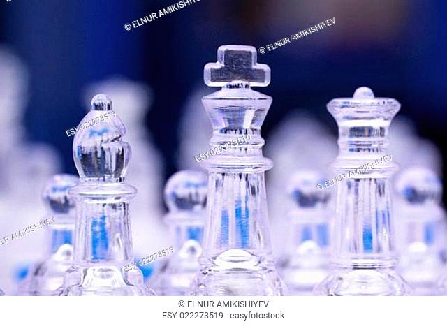 Glass chess figures against blurry background