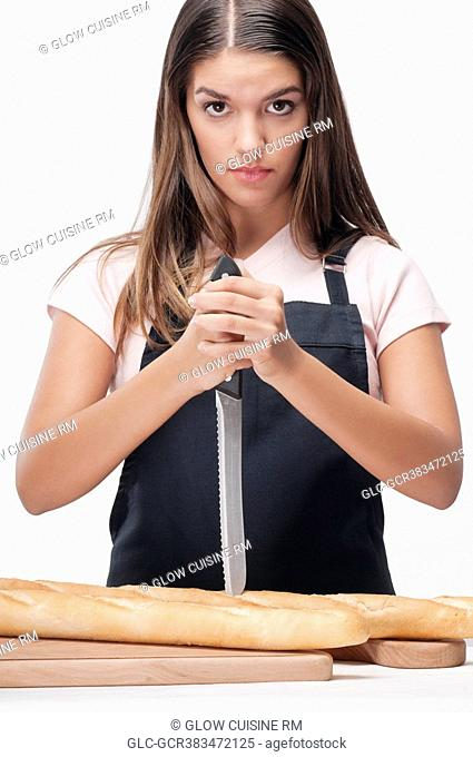 Woman cutting baguettes and thinking