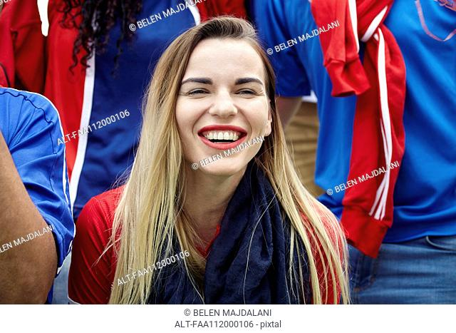 Woman watching football match, smiling cheerfully