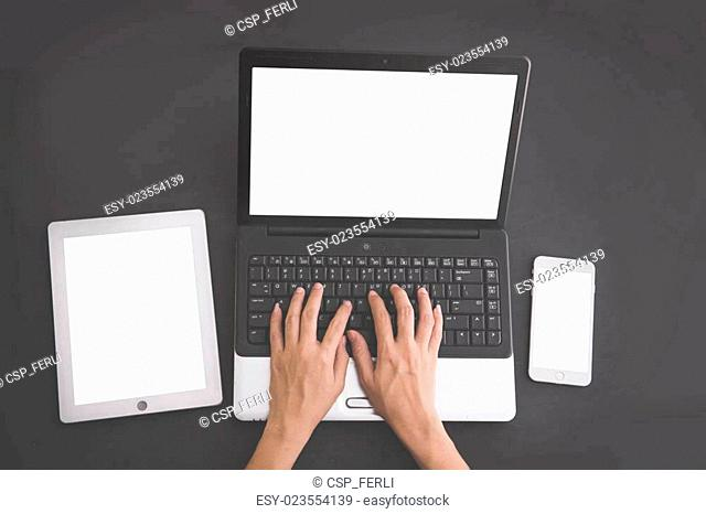 Hands typing on laptop with tablet and mobile phone on the side. on black background, mock up