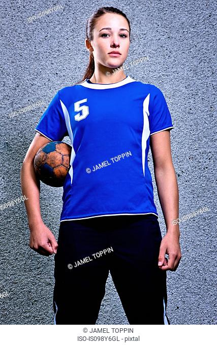Portrait of young woman holding handball