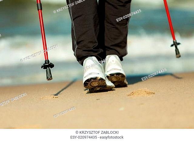 Nordic walking. Female legs hiking on the beach