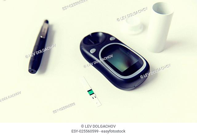 medicine, diabetes and health care concept - close up of glucometer with stick and blood sugar test stripes container on table