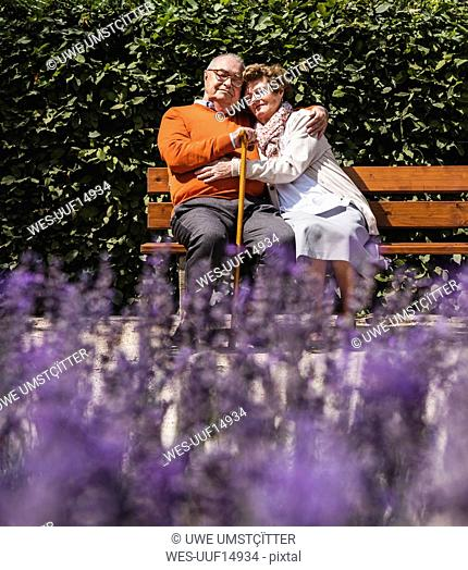 Senior couple sitting on bench in a park, with arms around