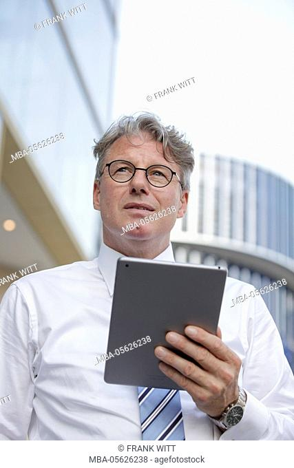 Businessman with iPad in front of office building